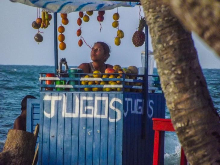 On the beach in Puerto Viejo (Near Covenas, Colombia) I saw this image that to me represents the reality for many in Colombia, no matter how hard the odds somebody will do something to sustain their family in this case selling natural juices. There is very little public aid in Colombia.En la playa de Puerto Viejo (cerca de Covenas, Colombia) Vi esta imagen de una joven que para mi representa los sacrificios que muchos tienen que hacer en Colombia para sobrevir. En Colombia no existe un sistema de ayuda publica como el que tenemos aqui.